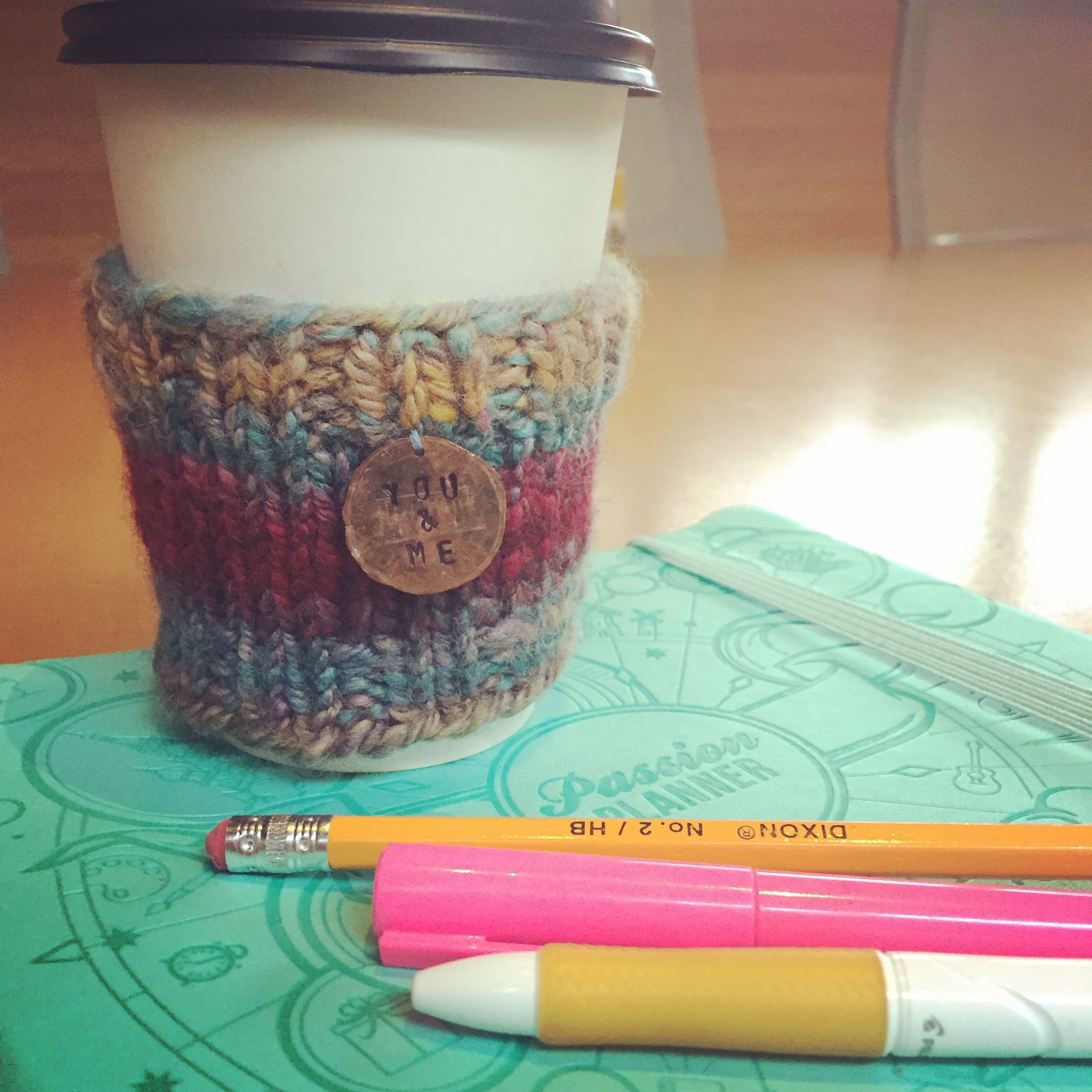 Image of a coffee cup with a planner and pens