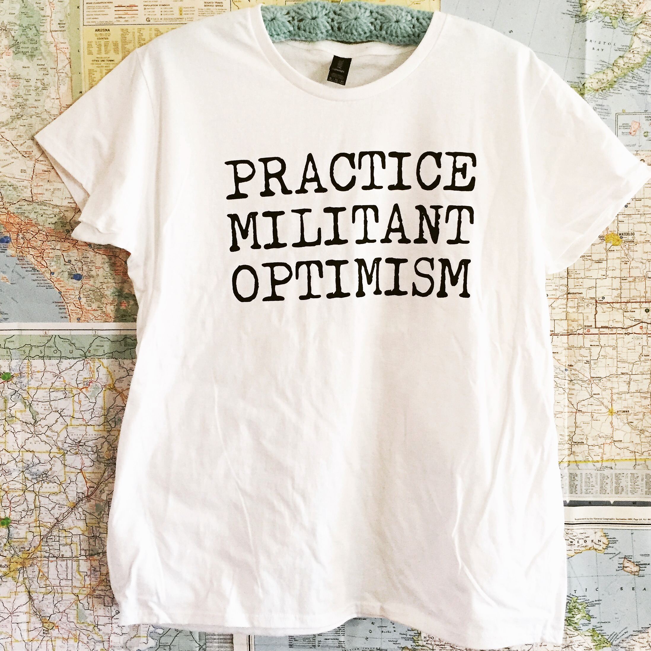 Image of a shirt that reads Practice Militant Optimism