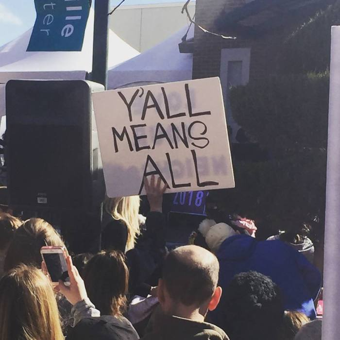 Image of crowd with a sign that says Y'all Means All